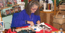 Joan Wells demonstrating the making of feather jewelry.